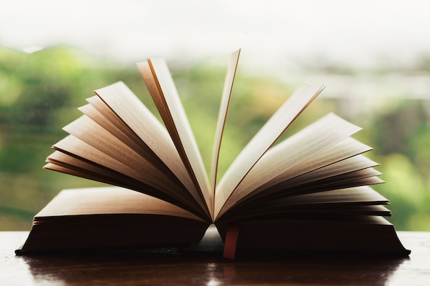 Öffnen sie bibelmorgenandacht auf holztisch mit fensterlicht