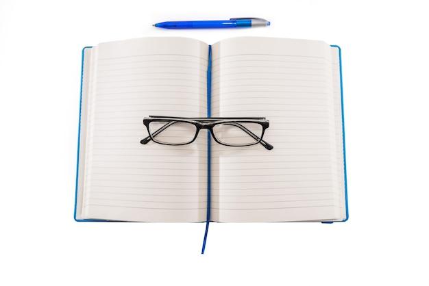 Öffnen sie blaues notizbuch, stift und brille isoliert auf weißem hintergrund. von oben betrachten. flach liegen. kopie des leerzeichens