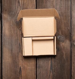 Öffnen sie braune pappkarton auf holztisch, draufsicht