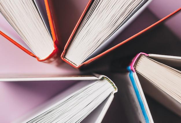 Öffnen sie bücher auf einem rosa hintergrund. machen sie sich mit dem bildungs- und lesekonzept vertraut. literatur für lernen, entwicklung und freude