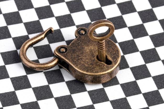 Öffnen sie das bronzeschloss mit dem schlüssel über dem schachhintergrund