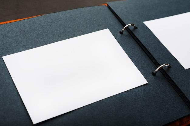 Öffnen sie das fotoalbum mit leerem platz für fotos, weißen rahmen auf schwarzem papier. das albumcover besteht aus braunem handgefertigtem echtleder