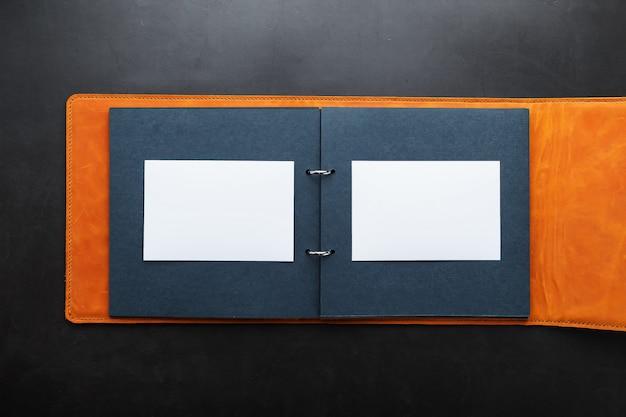 Öffnen sie das fotoalbum mit leerem platz für fotos, weißen rahmen auf schwarzem papier. das albumcover besteht aus braunem handgefertigtem echtleder.