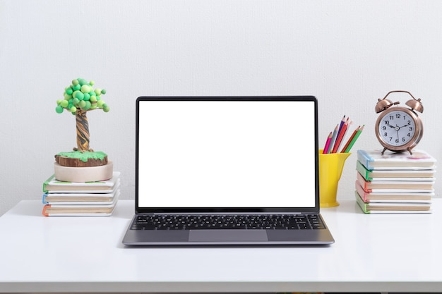 Öffnen sie das laptop-modell am arbeitsplatz des kindes mit büchern und buntstiften. zurück zum schul-online-lernkonzept