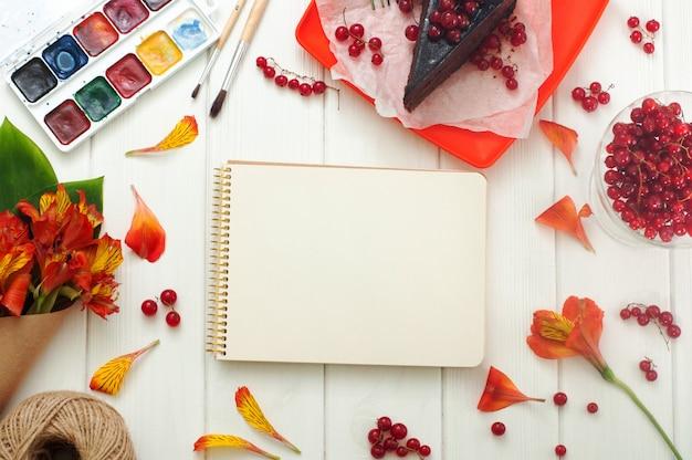 Öffnen sie das leere notizbuch mit dem roten aktuellen kuchenstück