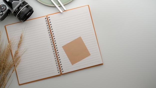 Öffnen sie das leere notizbuch mit der haftnotiz auf dem esstisch mit kamera, teller, besteck und kopierraum