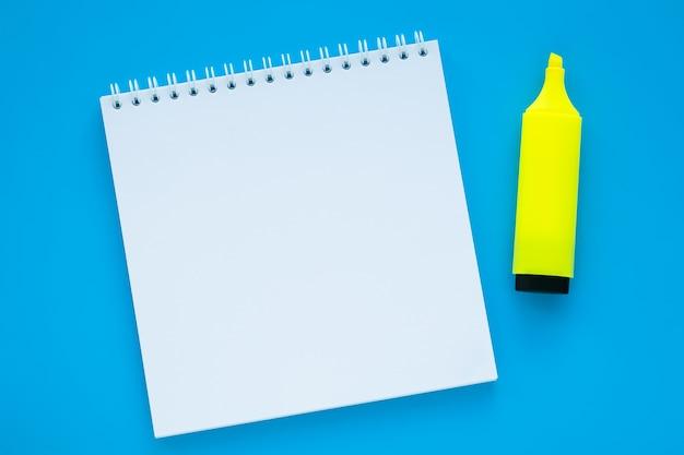 Öffnen sie das leere notizbuch und den marker auf blauem hintergrund.