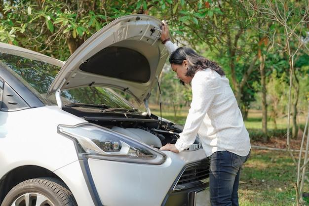Öffnen sie das motorsystem des motorhaubenmechanikers, um einen beschädigten autounfall zu überprüfen und zu reparieren.