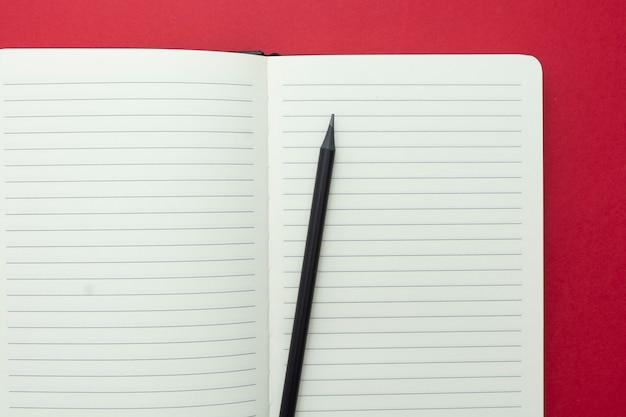 Öffnen sie das notizbuch, das auf rotem hintergrund lokalisiert wird, kopieren sie raum für text.