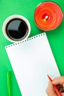 Öffnen sie das notizbuch, die hand eines mannes und ein glas mit einem kohlensäurehaltigen getränk auf grünem weihnachtshintergrund. dekoration des neuen jahres.