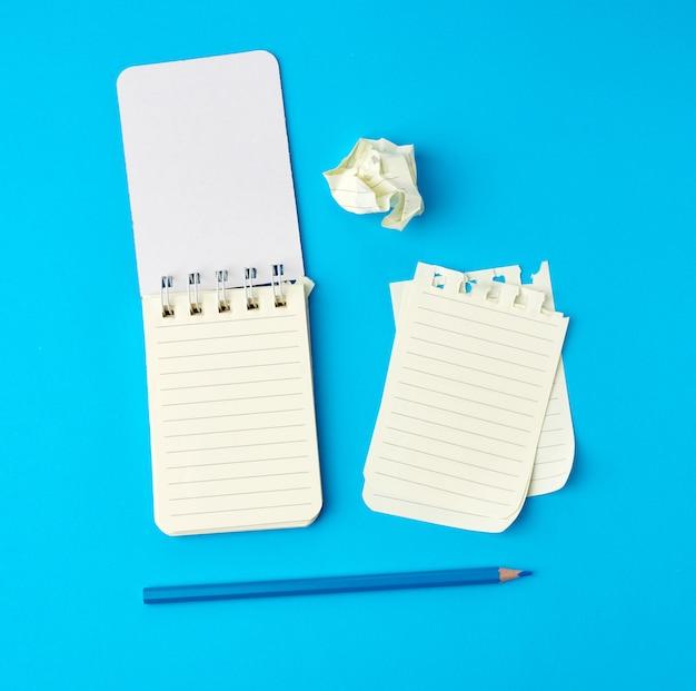 Öffnen sie das notizbuch in einer reihe und einen blauen holzstift neben zerrissenen und zerknitterten seiten