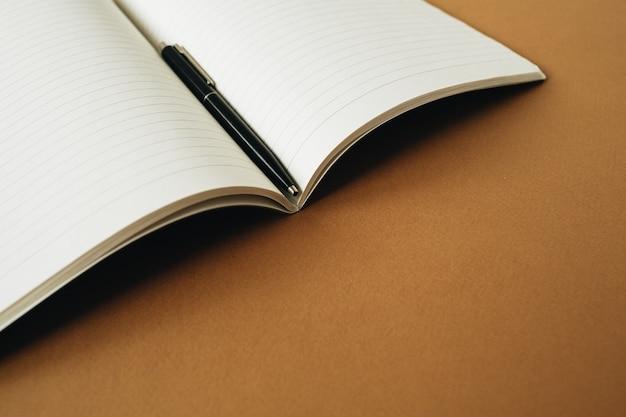 Öffnen sie das notizbuch mit einem stift auf ingwerorange