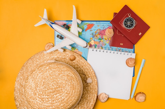Öffnen sie das notizbuch mit reiseaccessoires auf gelbem grund. sommerferien planen, reisen