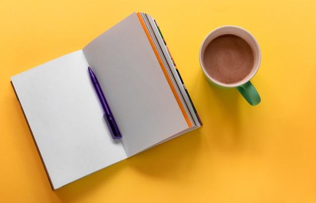 Öffnen sie das notizbuch / skizzenbuch mit stift und tasse kaffee auf gelb