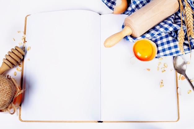 Öffnen sie das notizbuch und die grundlegenden backzutaten