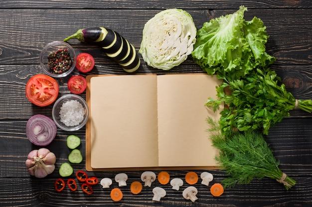 Öffnen sie das rezeptbuch und verschiedene frische bio-gemüse
