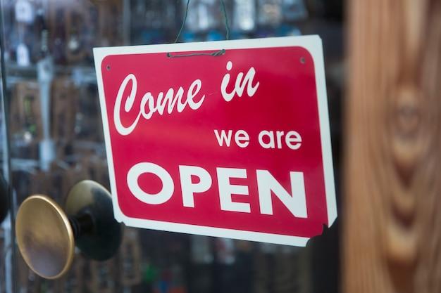 Öffnen sie das schild am glas des laden- oder caféfensters