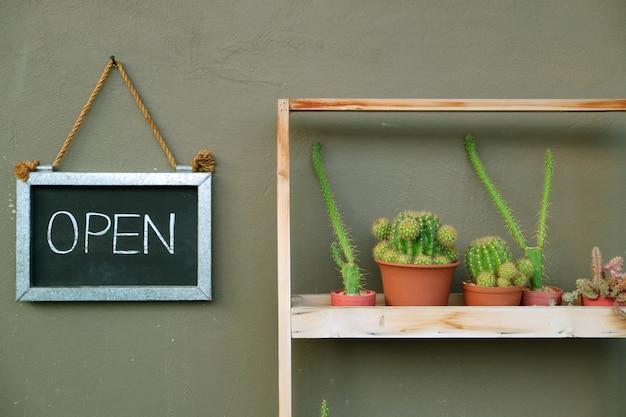 Öffnen sie das schild, das an der caféaußenwand neben dem saftigen pflanzenregal hängt