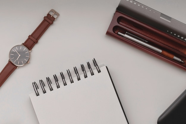 Öffnen sie das weiße spiralblock mit einem leeren blatt und viel bürozubehör, einer armbanduhr, einem mobiltelefon, einer federtasche und einem laptop.