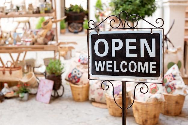 Öffnen sie das willkommensschild vor einem marktgeschäft