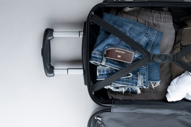 Öffnen sie den koffer, der für das reisen mit thailand-pass auf grauem hintergrund verpackt wird