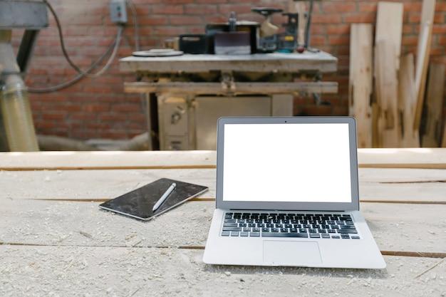 Öffnen sie den laptop in einem holzgeschäft mit isoliertem bildschirm