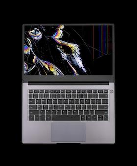 Öffnen sie den laptop mit einem kaputten bildschirm in farbflecken und rissen, die auf schwarzem hintergrund isoliert sind, nahaufnahme von oben
