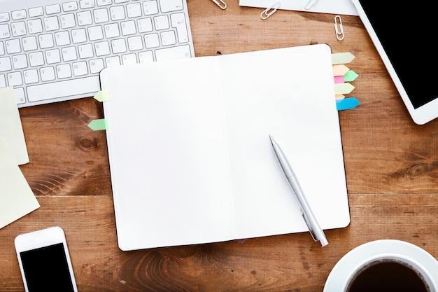 Öffnen sie den notebook-organizer auf dem computertisch mit kaffeezubehör