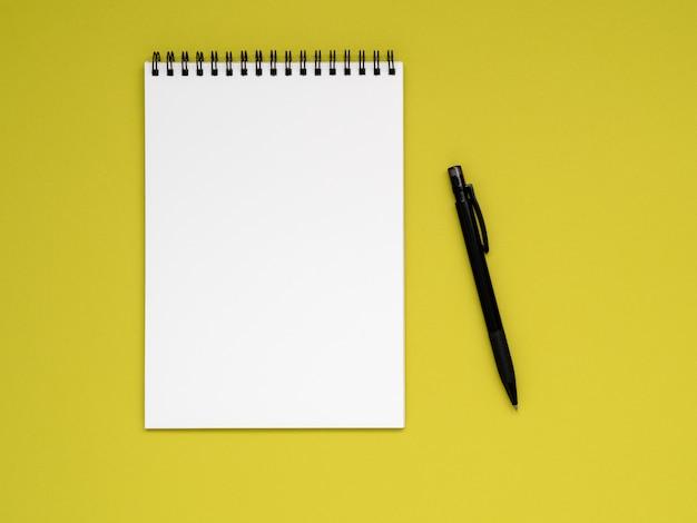 Öffnen sie den notizblock auf der spirale mit einer sauberen weißen seite und einem bleistift auf einer hellen gelben hintergrundfarbe