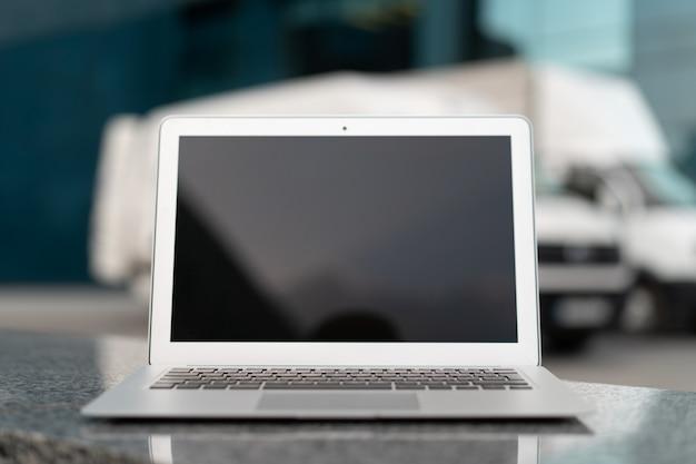 Öffnen sie den schwarzen bildschirm des laptops mit bürogebäude und lkw im hintergrund versandbereich logistikkonzept, das fahrzeugtransportservice liefert
