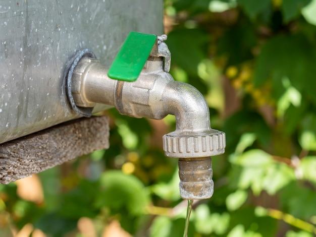 Öffnen sie den wasserhahn oder tippen sie mit fließendem wasser in unscharfem gartenhintergrund