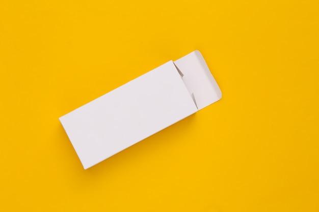 Öffnen sie den weißen verpackungskarton auf gelb. minimalismus