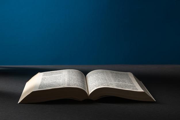 Öffnen sie die bibel in einer dunkelheit in einem lichtstrahl.