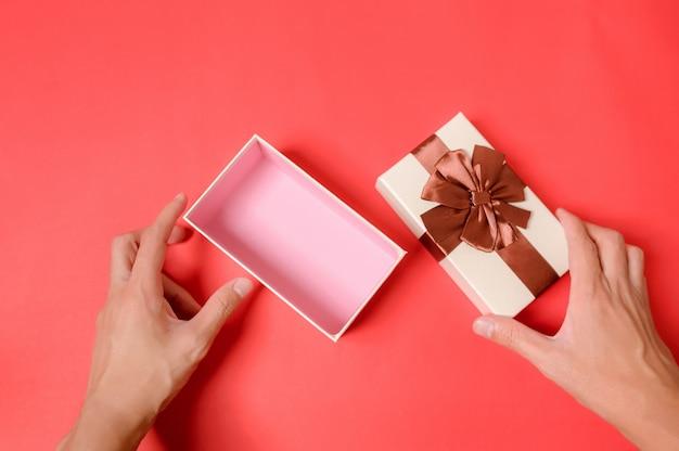 Öffnen sie die geschenkbox mit einer hand.