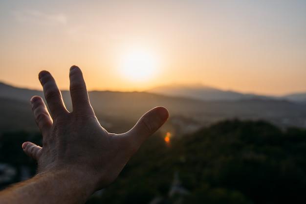 Öffnen sie die hand in richtung horizont mit einem wunderschönen sonnenuntergang