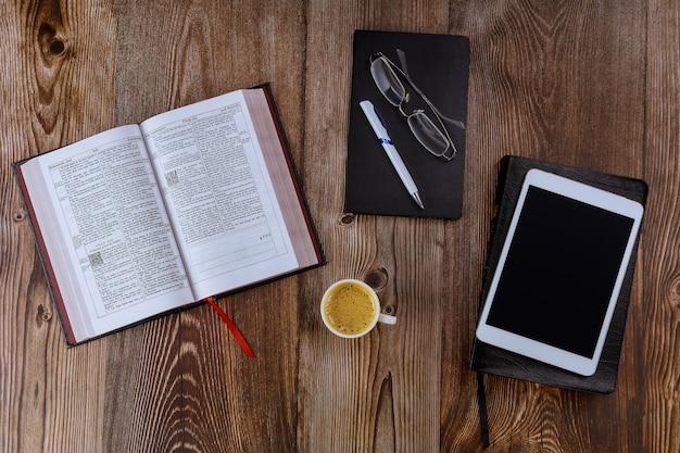 Öffnen sie die morgenlesungen der heiligen bibel auf einer tischplatte auf dem digitalen tablet mit einer tasse kaffee
