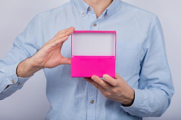 Öffnen sie die rosa schachtel in den händen der männer. vorderansicht. speicherplatz kopieren. attrappe, lehrmodell, simulation.