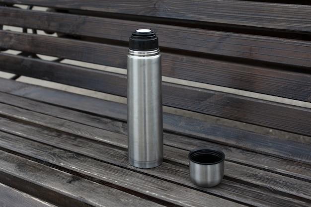 Öffnen sie die stahlmetallthermosflasche mit tee oder kaffee auf einer holzbank.