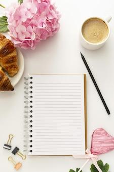 Öffnen sie ein leeres notizbuch, eine tasse kaffee, ein croissant und eine rosa hortensie.