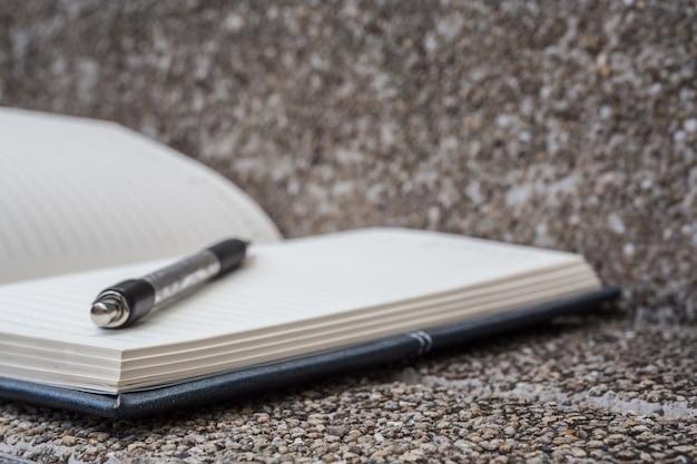 Öffnen sie ein leeres weißes notizbuch, stift mit vintage-filter