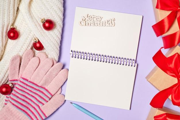 Öffnen sie einen leeren notizblock auf violettem hintergrund mit einem schal, handschuhen, geschenkboxen und weihnachtskugeln