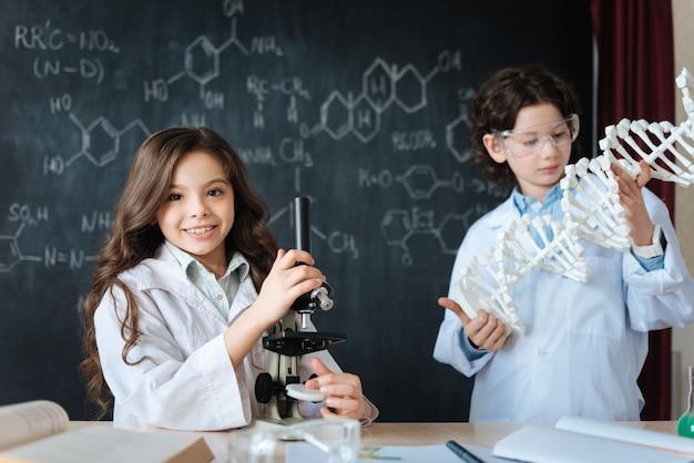Öffnen sie gemeinsam neue wissenschaftliche horizonte. erfreute erfinderische, charmante kinder, die im labor stehen und chromosomenmodifikationen erforschen, während sie am biologieprojekt teilnehmen und studieren