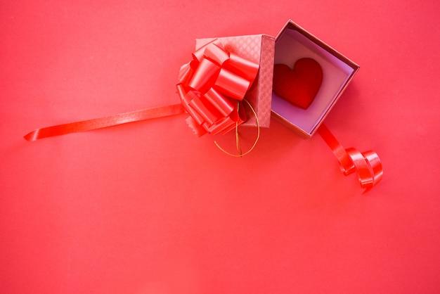 Öffnen sie geschenkbox und rotes herz im roten kasten der überraschung des kastens mit bandbogen für geschenk valentinsgrußtag
