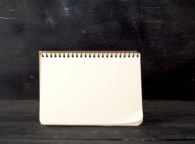 Öffnen sie gewundenes notizbuch mit leeren weißen blättern gegen ein schwarzes kreidebrett