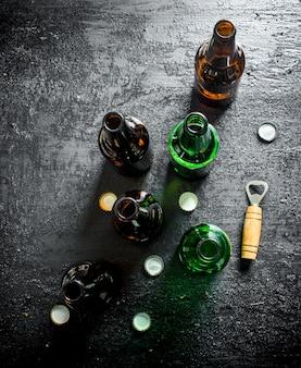 Öffnen sie glasbierflaschen und öffner. auf schwarzem rustikalem hintergrund