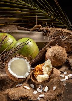 Öffnen sie grüne kokosnüsse und reife kokosnüsse mit süßer kokosnuss auf dem tisch