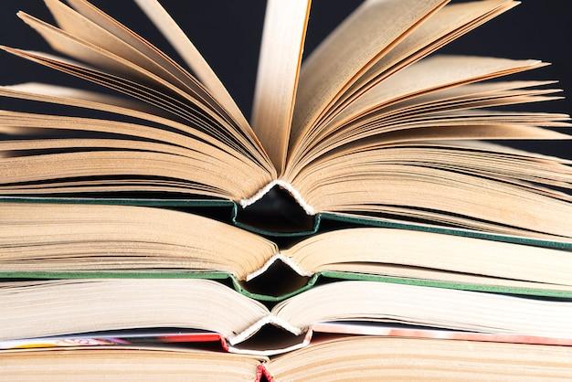 Öffnen sie hardcover-bücher. stapelung von büchern ohne inschriften aufeinander, leerer buchrücken. zurück zur schule. öffne das buch