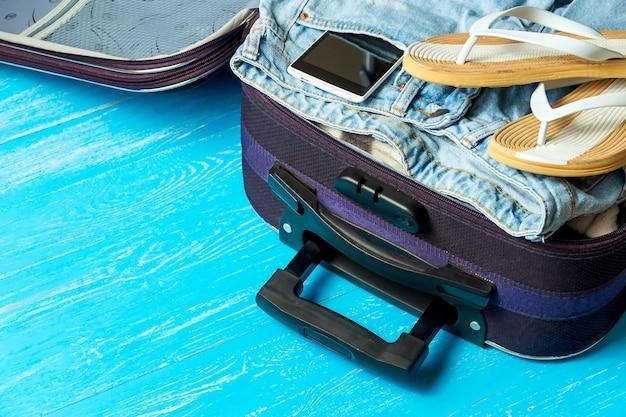 Öffnen sie koffer mit reisezubehör auf blauem holztisch