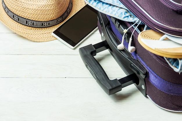 Öffnen sie koffer mit reisezubehör auf weißem holztisch