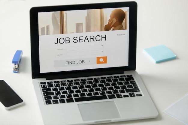 Öffnen sie laptop auf dem schreibtisch, job suchen titel auf dem bildschirm